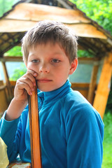 Pensive boy in the summer of wooden gazebo