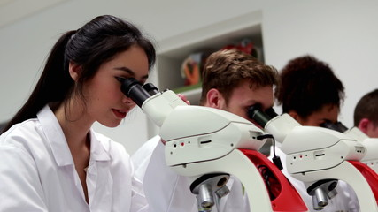 Pretty medical student looking through microscope then smiling