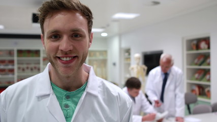 Handsome medical student smiling at camera in class
