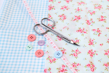 Sewing tools and vintage fabric background with scissors