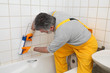 Worker plumber caulking bath tube and tiles with silicone glue