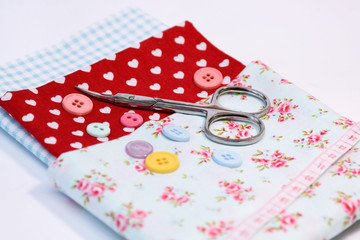 Sewing tools with vintage fabric background with scissors