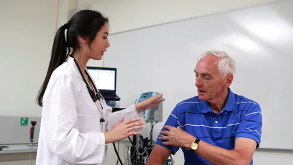 Doctor talking to patient with shoulder pain