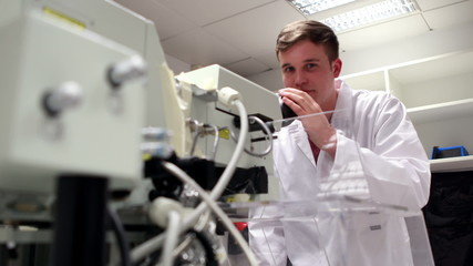Young science student looking through high powered microscope