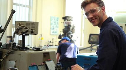 Young mechanic smiling at camera
