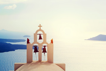 Traditional bells and cross over Aegean sea. Santorini Greece