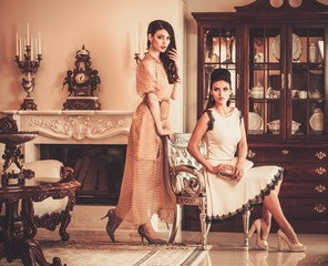 Two young women in luxury house interior