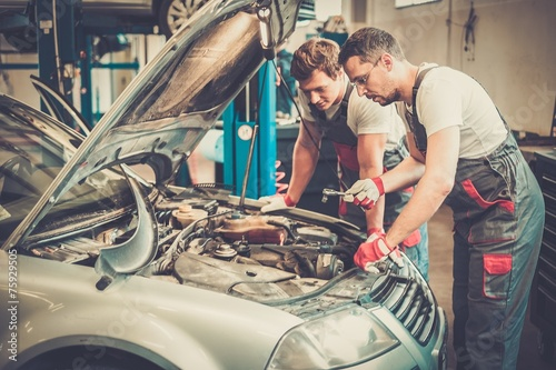 Two mechanics fixing car in a workshop - 75929505
