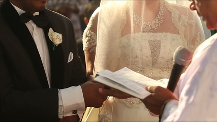 Catholic priest imposes a blessing for the bride and groom hands