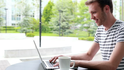 Smiling student drinking coffee and typing on laptop