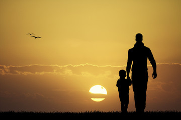 Father and son silhouette at sunset