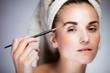 Fresh model girl applying make up with brush
