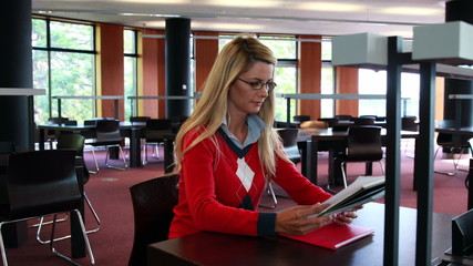 Mature student with reading glasses studying at library desk