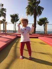 Bimba che gioca e salta su tappeto elastico