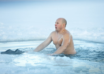 Winter swimming. Man in ice-hole