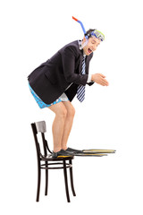 Businessman with snorkel jumping off a chair