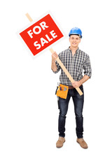Young male engineer holding a for sale sign