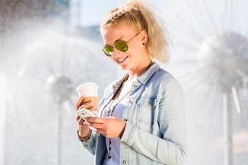 Frau mit Telefon und Kaffee am Brunnen