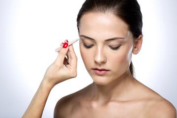 Beautiful young woman plucking eyebrows