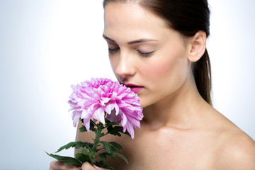 Beautiful woman smelling flowers over gray background