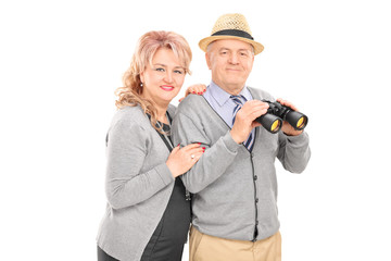Mature couple posing with binoculars