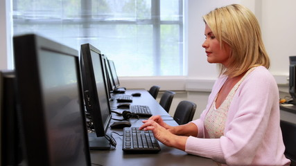 Woman typing at computer while smiling at the camera