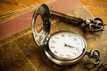 pocket watch key and old book