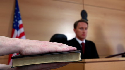 Judge looking at the witness swearing on bible