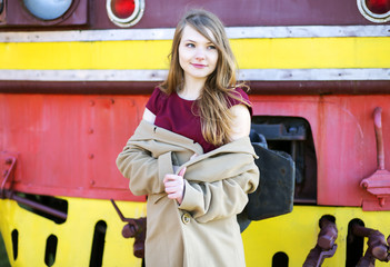 Woman in beige coat before train front