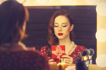 Portrait of a beautiful woman as applying makeup near a mirror