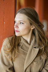 Woman in beige coat with confident face