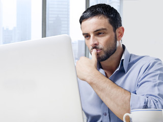 attractive businessman working on computer at office desk