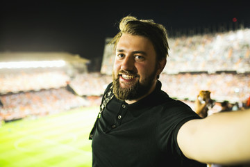 Handsome supporter making selfie at football game in Barcelona