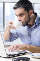 attractive businessman drinking coffee cup at office desk