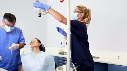Dentist talking with patient while nurse prepares the tools