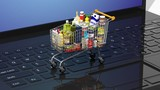 Full with products supermarket shopping cart on keyboard