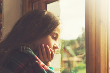 Adorable little girl dream in cold sunny morning. Toned