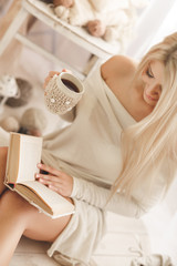 Young woman reading a book with a Cup of coffee in his hands.