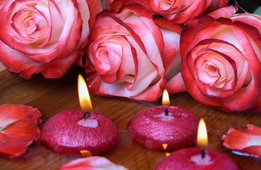 Spa concept with roses and burning candles that float in the wat