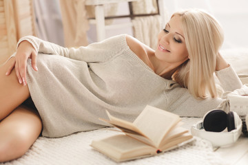 Woman reading a book lying on the sofa.