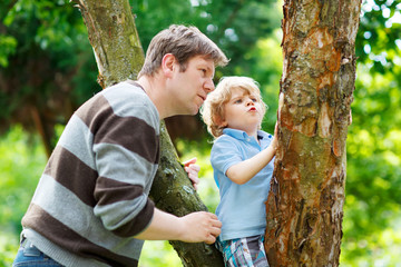 Cute little kid boy enjoying climbing on tree with father, outdo