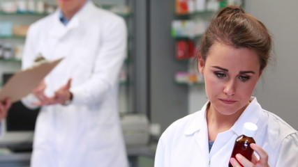 Pharmacist looking at medicine jar