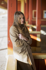 Woman in coat feel cold at station