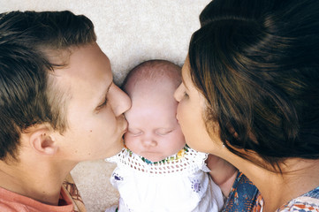 Young couple kissing their newborn baby.