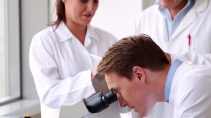 Chemist looking at a microscope with colleagues behind him