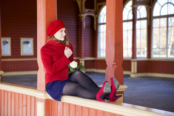 Woman on boundaries adjust red coat collar