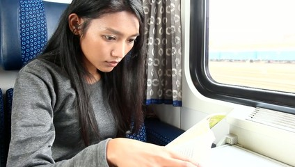 woman read her book while traveling by train