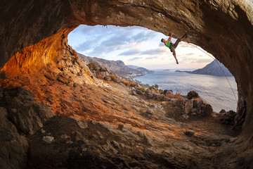 Young man lead climbing in cave before sunset