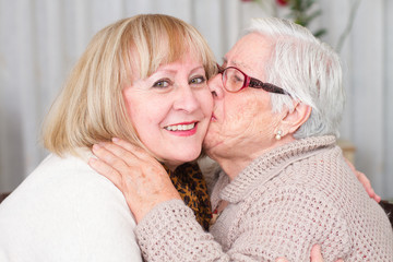 grandmother kisses her daughter