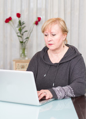 Middle age woman using computer at home